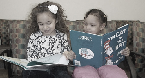 Photo of two young girls reading books
